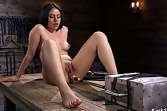Brunette fucks machine on a wooden table