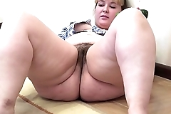 A fat skirt with a hairy fur pie masturbates with a cucumber